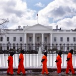 protesters in orange jumpsuits parade in front of whitehouse blanketed in snow.