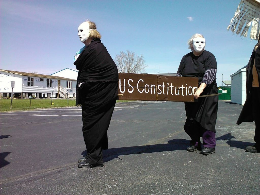 "drone protesters carry coffin labeled ""US Constitution"""
