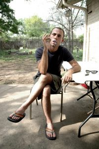 Brandon Darby sits on a patio blowing smoke rings