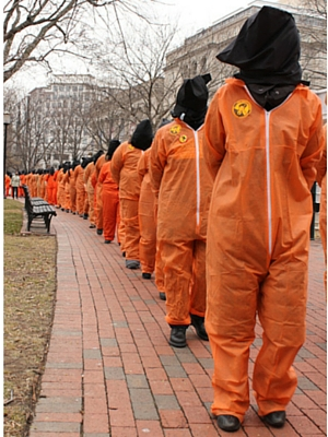 protesters dressed in orange jumpsuits and black hoods at Close Guantanamo protest in Washington, DC