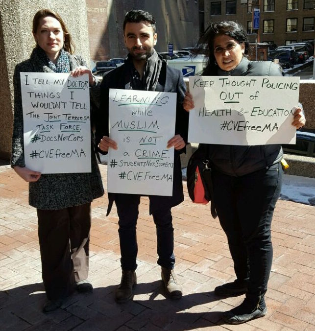 "activists with signs such as ""Learning while Muslim is not a crime"" and #CVEFreeMA"