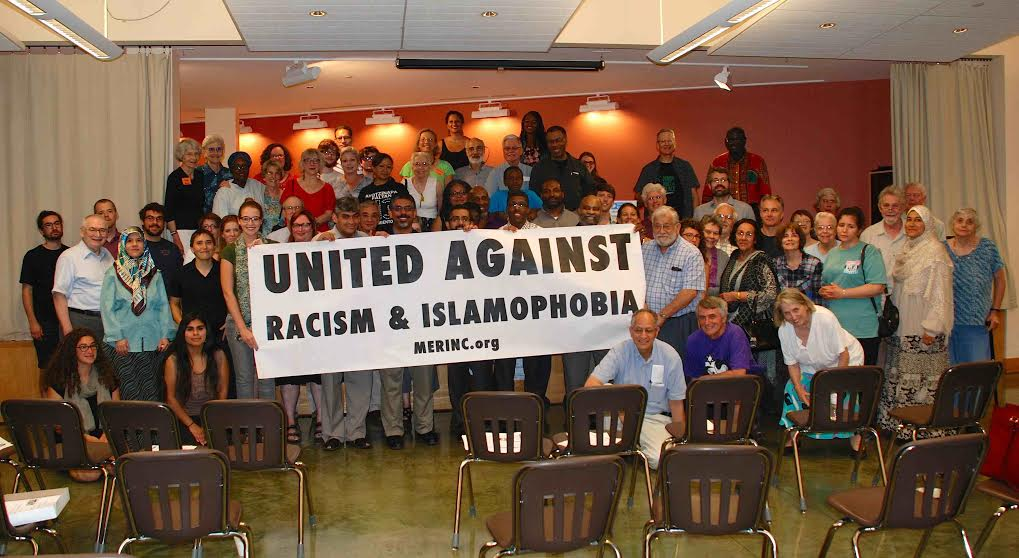 "conference attendees gather around sign ""United Against Racism & Islamophobia"""