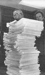Frank Wilkinson stands behind a stack of papers - his FBI file that is as tall as he is