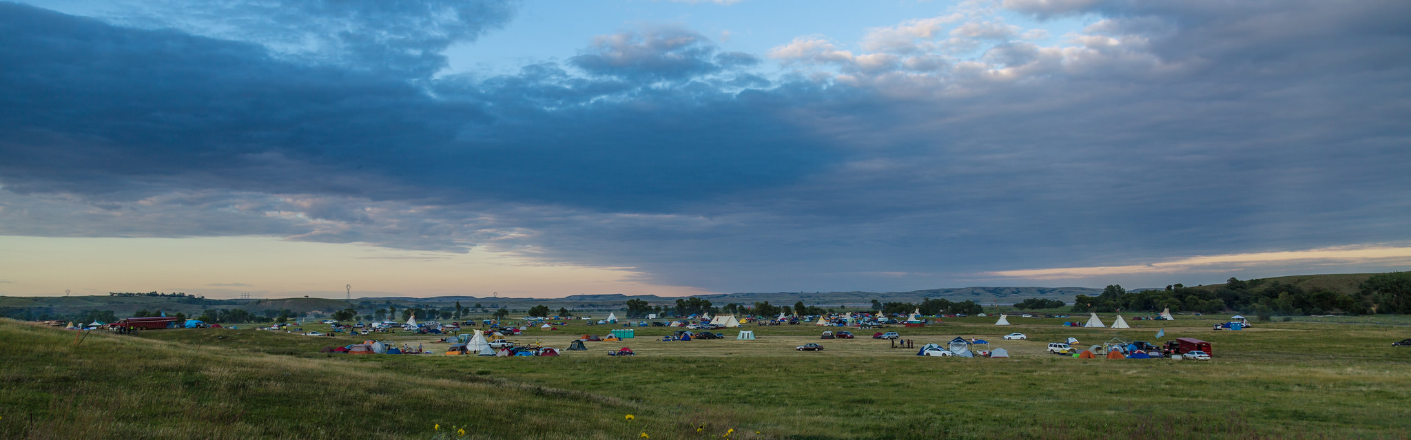 broad view of sky and prairie with tents and camping vehicles