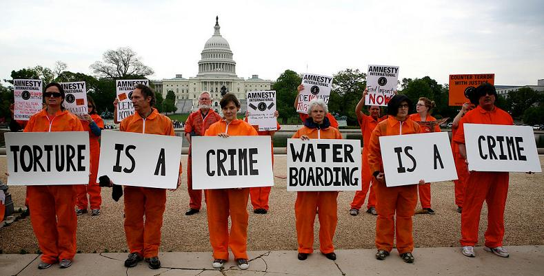 protest at capitol with orange jumpsuits and signs torture is a crime