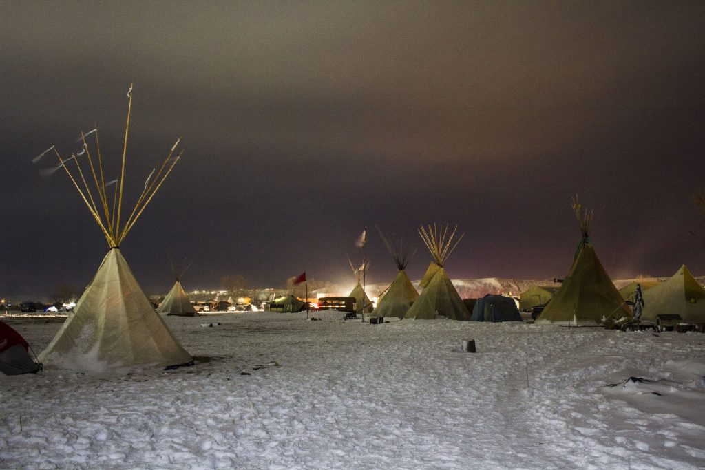 teepees at Standing rock at night back lit by headlights