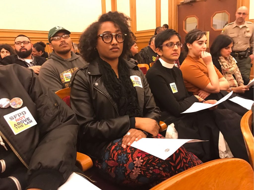 "people at city council meeting with stickers that say ""SFPD not above the law"""