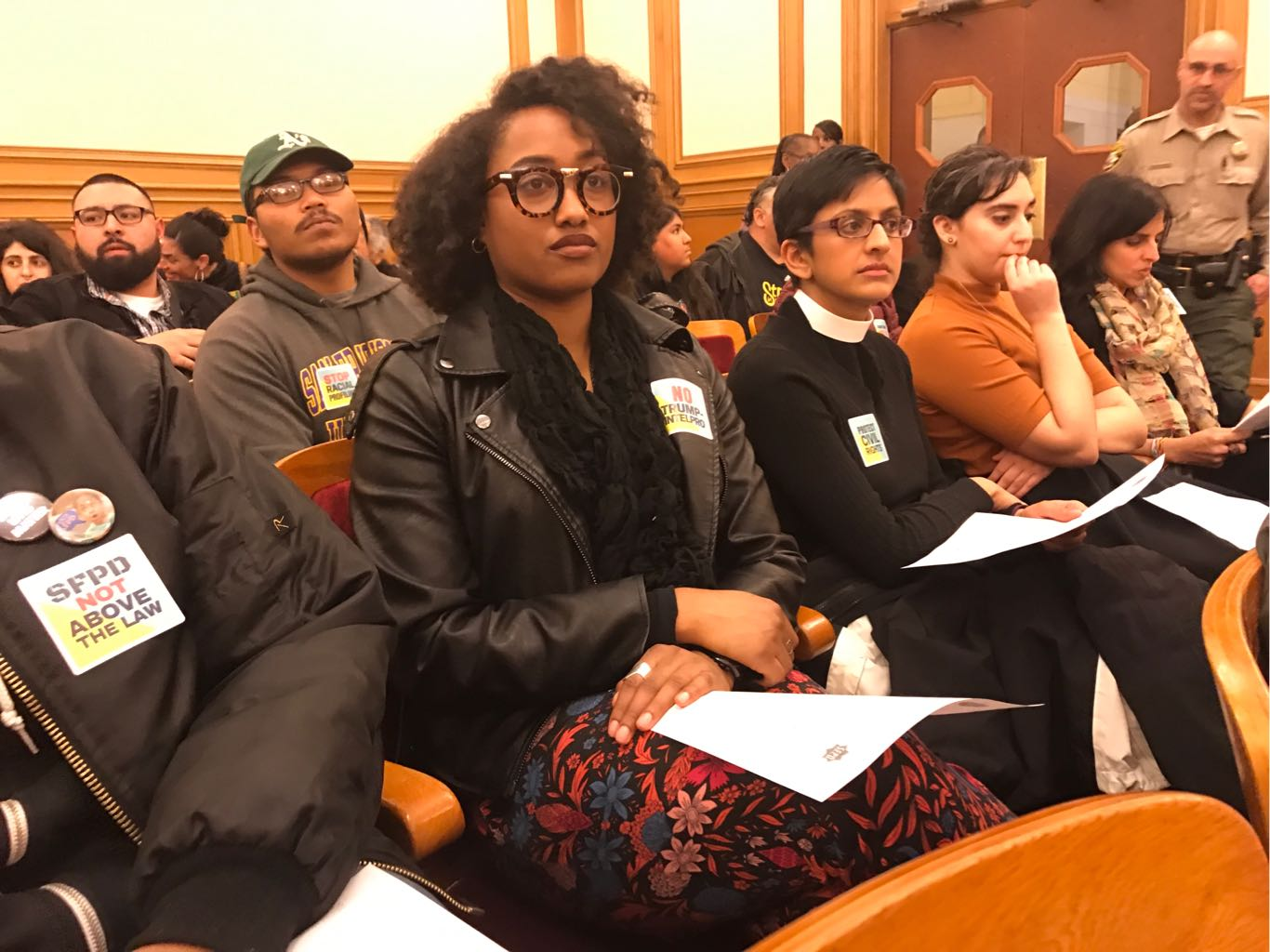 """people at city council meeting with stickers that say """"SFPD not above the law"""""""