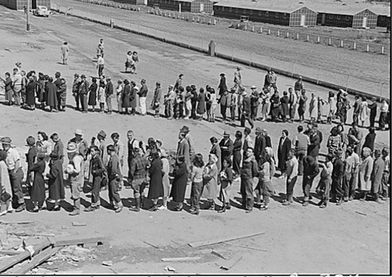 San Bruno, California. This assembly center has been open for two days. Bus-load after bus-load of evacuated persons of Japanese ancestry are arriving on this day after going through the necessary procedures, they are guided to the quarters assigned to them in the barracks. Only one mess hall was operating today. Photograph shows line-up of newly arrived evacuees outside this mess hall at noon. Note barracks in background, just built, for family units. There are three types of quarters in the center of post office. The wide road which runs diagonally across the photograph is the former racetrack.