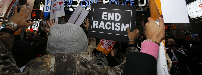 times square protest with sign says End Racism