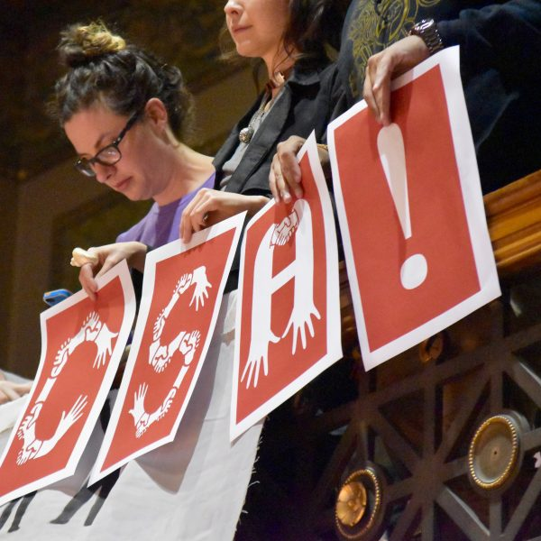 activists hold up signs at city council meeting