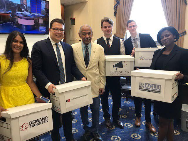 activists with boxes of petitions with Rep. John Conyers