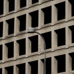 close up of the FBI HQ shows cracks in cement and Brutalist features