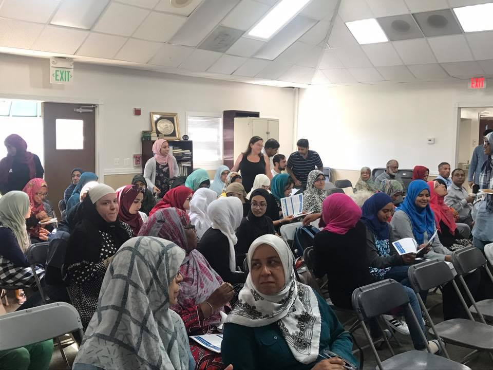 room full of mostly women, many young and most in hijab