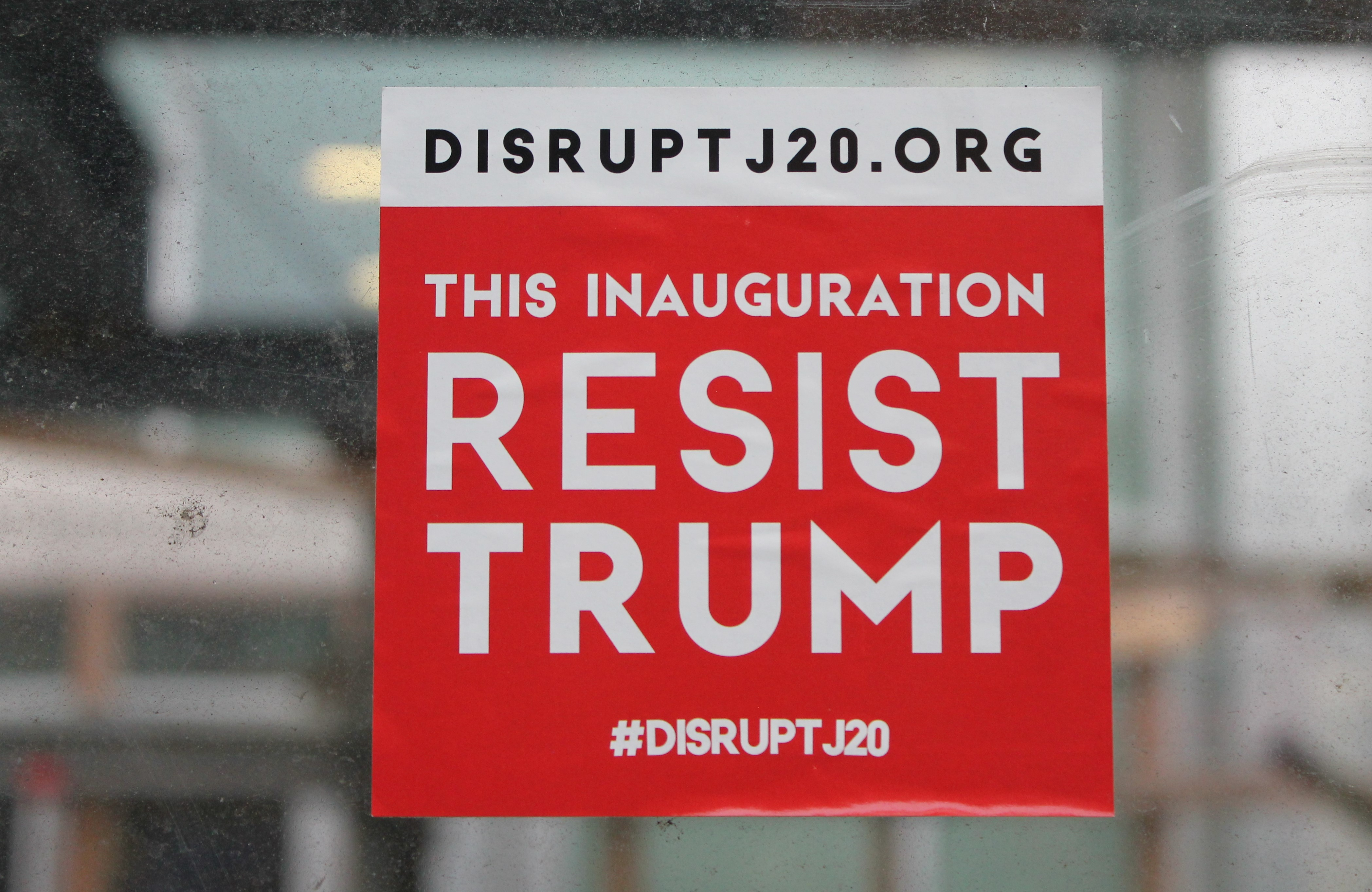"sticker at construction site in DC says ""resist Trump"" with Disrupt J20 website"