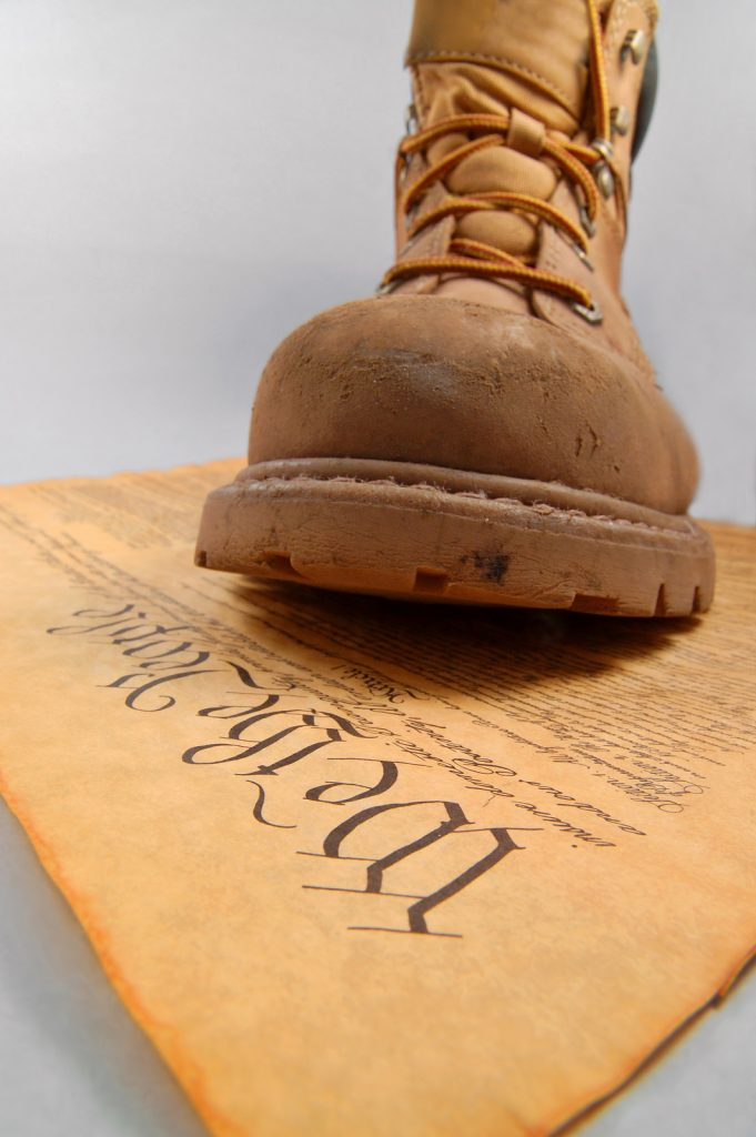 Boot of oppression stepping on the U.S. Constitution