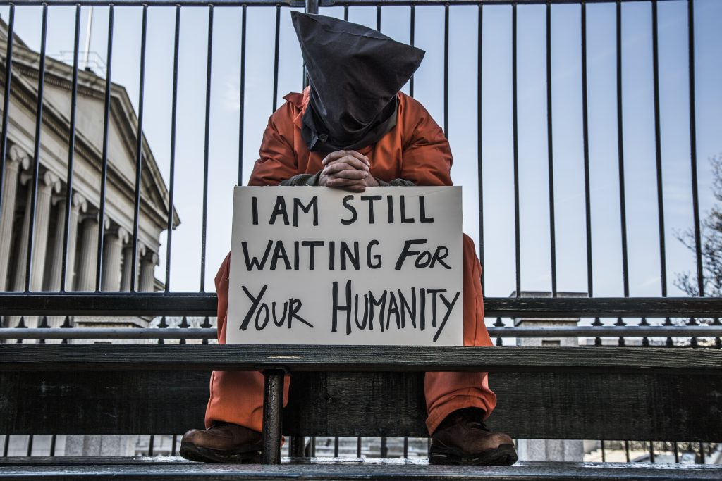 "protester dressed in hood an orange jumpsuit with sign ""I am still waiting for your humanity"" in front of the white house"