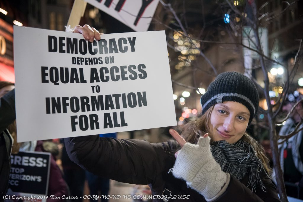 "Woman holding sign ""Democracy requires equal access to information for all"""