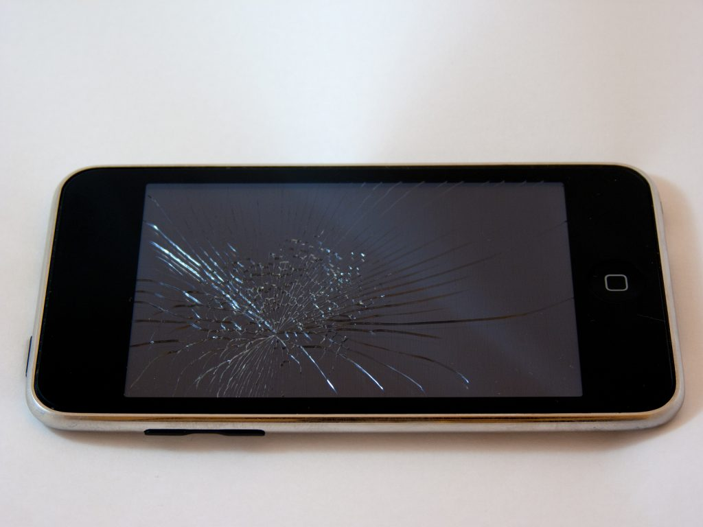 Broken Smartphone with a smashed screen on a white background