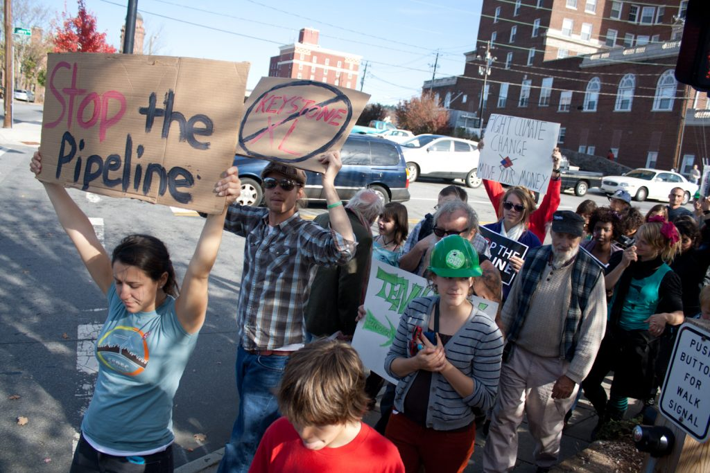 protesters march down the street with anti pipeline signs