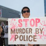 protester holds sign: stop murder by police