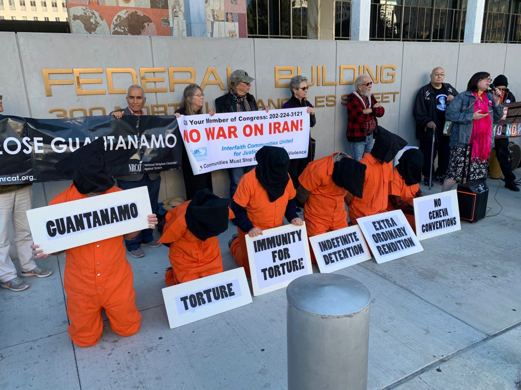 protesters in orange jumpsuits hold signs against guantanamo and torture