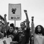 Young Black women with fists upraised at a protest